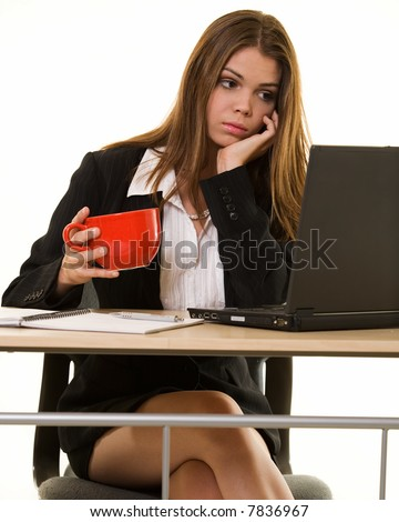 Attractive young brunette woman in business suit looking bored while looking at a computer screen while holding a red coffee mug - stock photo