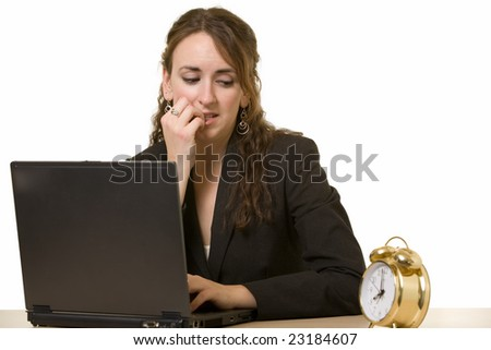 Attractive young brunette woman in business suit working at desk in front of laptop looking over at a round clock with worried expression biting fingernail