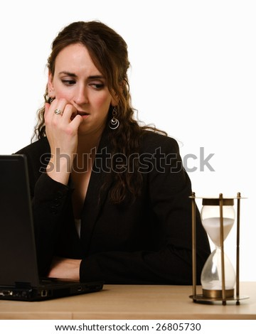 Attractive young brunette woman in business suit working at desk in front of laptop looking over at a hour glass with worried expression biting fingernails