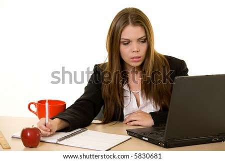 Attractive young brunette woman in business suit writing on a notebook sitting at a desk and looking at a computer screen - stock photo