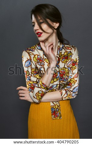 Attractive young brunette woman posing in clothes of camera with nice colorful clothes with flowers print.  - stock photo