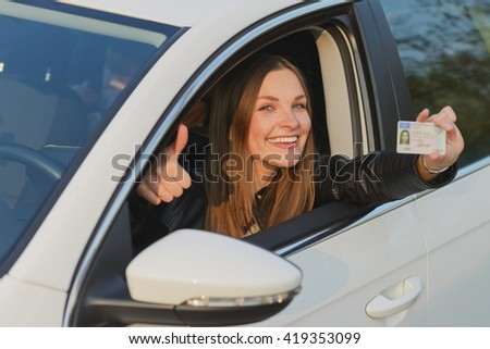 Attractive young brunette woman proudly showing her drivers license - stock photo