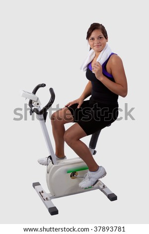 Attractive young brunette woman wearing workout attire sitting and pedaling on a stationary exercise bike - stock photo