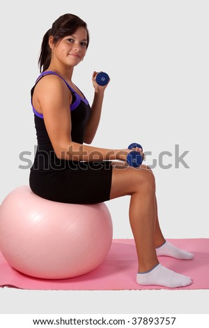 Attractive young brunette woman wearing workout attire sitting on a large pink exercise ball lifting weights over white