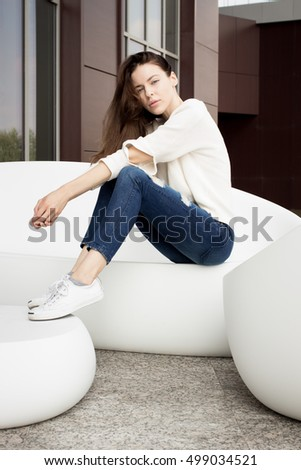 Attractive young brunette woman with pretty makeup, wearing casual street wear, sitting on white plastic sofa in front of tiles wall of the building