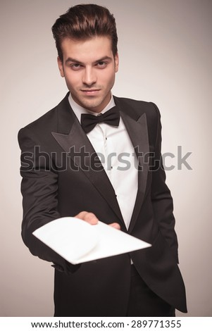 Attractive young business man holding one hand in his pocket while offering you a invitation. - stock photo