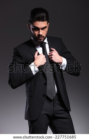 Attractive young business man looking at the camera while pulling his jacket. - stock photo