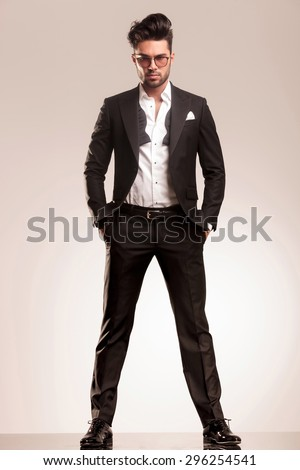Attractive young business man looking at the camera while standing with both hands in his pocket. - stock photo