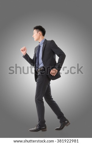 Attractive young business man running, full length portrait isolated. - stock photo
