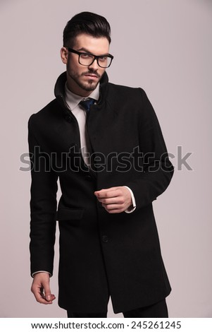 Attractive young business man wearing a elegant long coat, posing on studio background. - stock photo