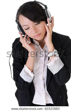 Attractive young business woman enjoying music by Mp3 player and headphone. - stock photo