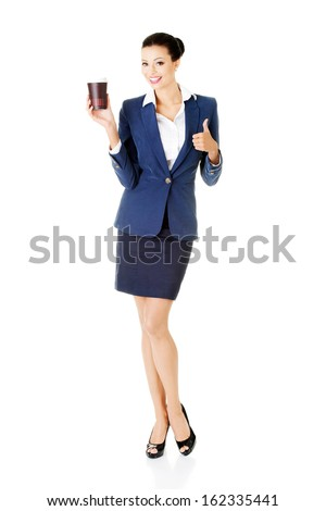Attractive young business woman holding a cup and showing OK. isolated on white.  - stock photo