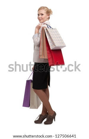 Attractive young business woman in a light beige suit holding shopping bags, isolated on white background