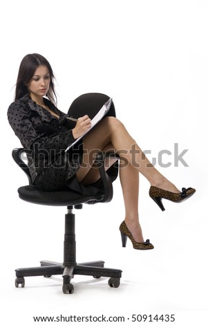 Attractive young business-woman is sitting and writing in the notebook - stock photo