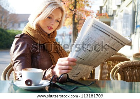 Attractive young business woman reading a newspaper at outdoor cafe - stock photo