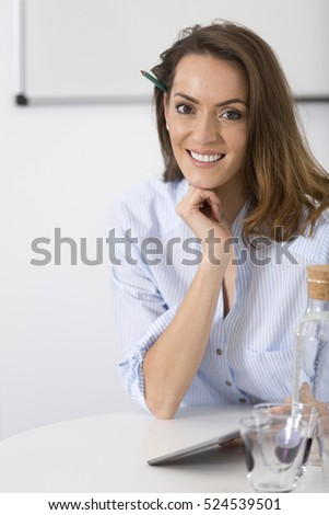 Attractive young business woman sat at her desk working and planning strategies