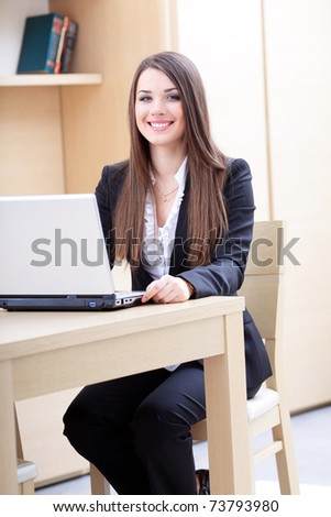 Attractive young business woman using laptop