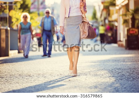 Attractive young business woman walking in the city - stock photo