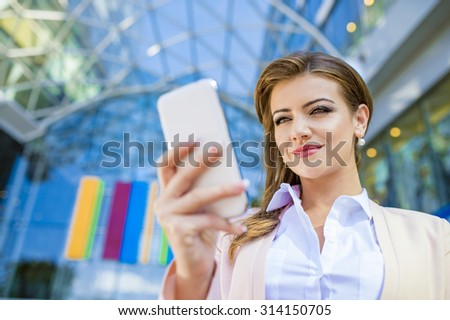 Attractive young business woman with smart phone - stock photo