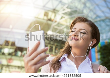 Attractive young business woman with smart phone in the city - stock photo