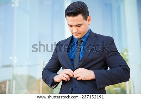 Attractive young businessman buttoning his jacket and fixing his suit before going into an important meeting - stock photo