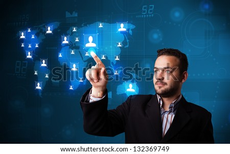 Attractive young businessman choosing from social network map - stock photo