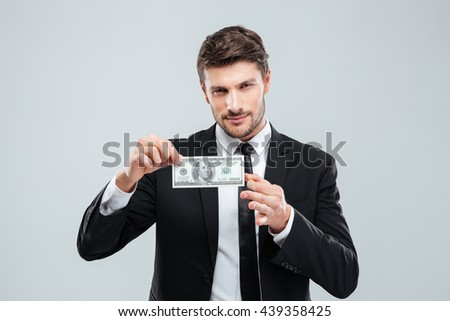 Attractive young businessman holding one hundred dollars banknote over white background - stock photo
