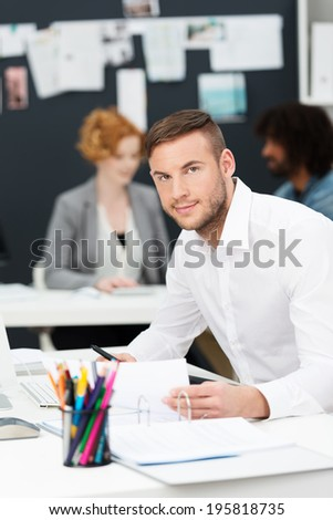 Attractive young businessman in a busy office sitting working at paperwork on his desk looking up at the camera