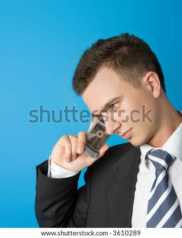 Attractive young businessman in black suit with mobile phone. More similar in my portfolio