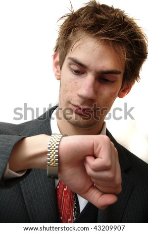 Attractive Young businessman in suit waits for his appointment and looks at his wrist watch for the time. Isolated on white background - stock photo