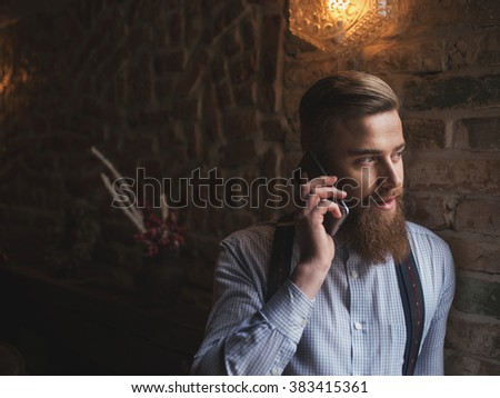 Attractive young businessman is communicating on telephone