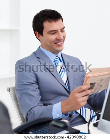 Attractive young businessman reading a newspaper in the office