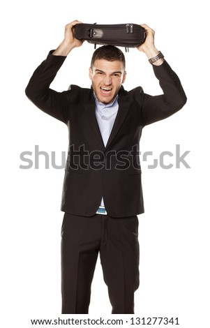 attractive young businessman screaming with a laptop bag over his head - stock photo
