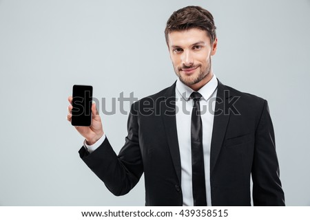 Attractive young businessman showing blank screen cell phone over white background - stock photo