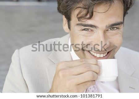 Attractive young businessman smiling at the camera while drinking a cup of coffee outdoors. - stock photo