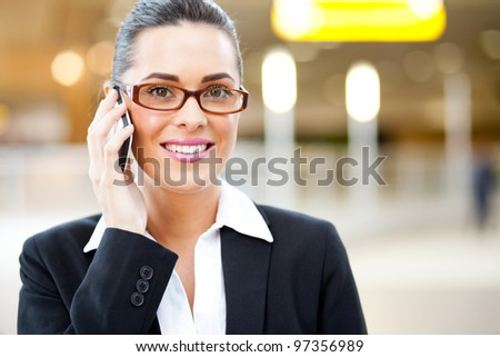 attractive young businessman talking on cellphone at airport
