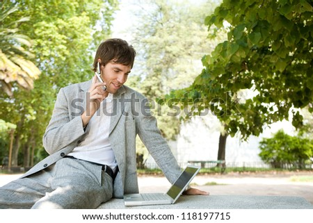 Attractive young businessman using a cell phone and a laptop computer and having a conversation over the phone while sitting on a bench in a city park, outdoors. - stock photo