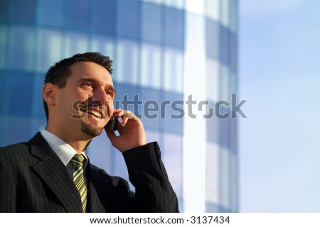 Attractive young businessman using a cell phone in front of a modern office building, smiling - stock photo
