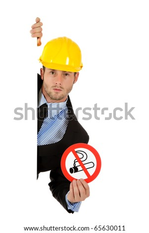 "Attractive young businessman with helmet, behind wall showing ""no smoking"" sign. Copy space. Studio shot. White background. - stock photo"