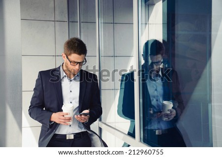attractive young businessman with phone device and coffee in hands on office building background - stock photo