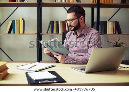 Attractive young businessman with the glasses focused reading book at home office - stock photo