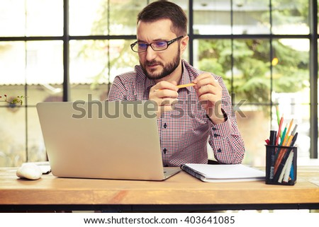 Attractive young businessman with the glasses looking at his laptop and take his pencil in hands - stock photo