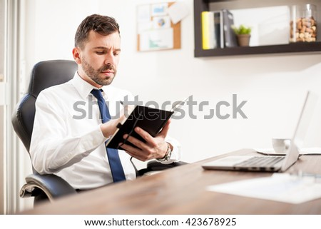 Attractive young businessman writing down some ideas on a notepad in his office