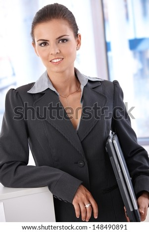 Attractive young businesswoman holding laptop, standing in office, smiling. - stock photo