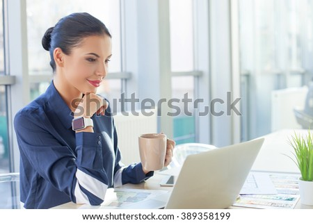 Attractive young businesswoman is enjoying hot tea