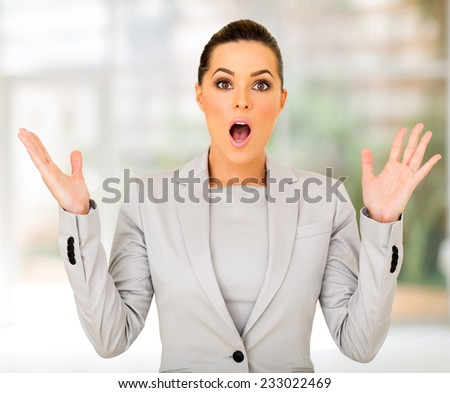 attractive young businesswoman looking surprised - stock photo