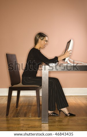 Attractive young businesswoman looking surprised at the contents on a computer. Vertical shot. - stock photo