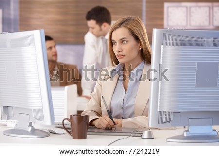 Attractive young businesswoman participating at computer training course, using tablet.? - stock photo