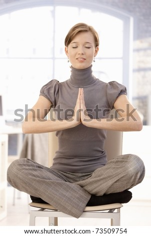 Attractive young businesswoman practicing yoga in office, meditating at lotus position. - stock photo