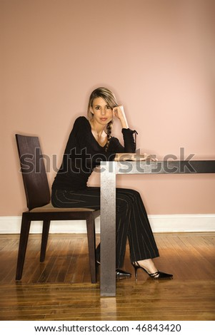 Attractive young businesswoman sitting at a table. She is resting her head on her hand. Vertical shot. - stock photo